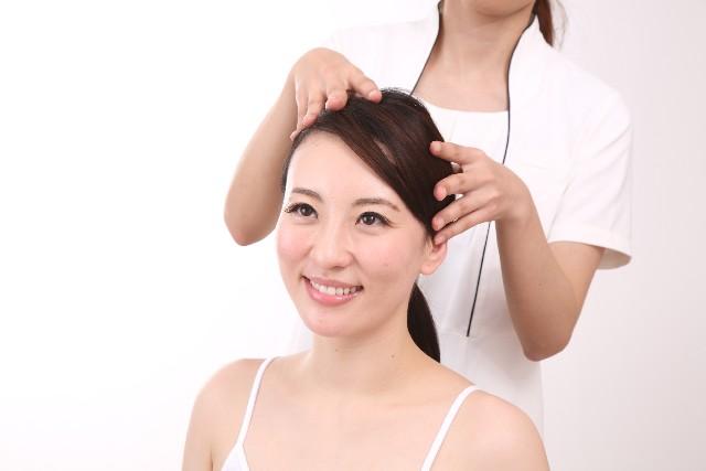 頭皮の指圧マッサージを受けている女性