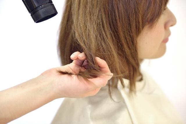 傷んだ髪にドライヤーを当てている女性