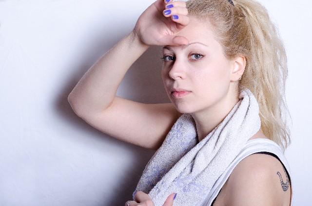 フィットネスをして額の汗を手で拭っている女性