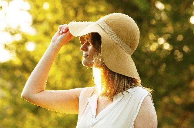 やわらかいハット型の帽子を深くかぶり日差しを防いでいる女性