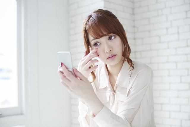 鏡で化粧の崩れを見ている女性