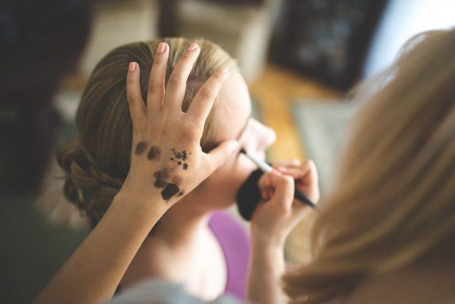 美容部員にメイクしてもらう女性