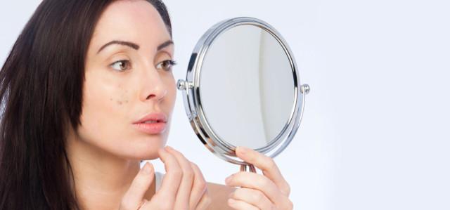 ニキビを鏡でチェックする女性