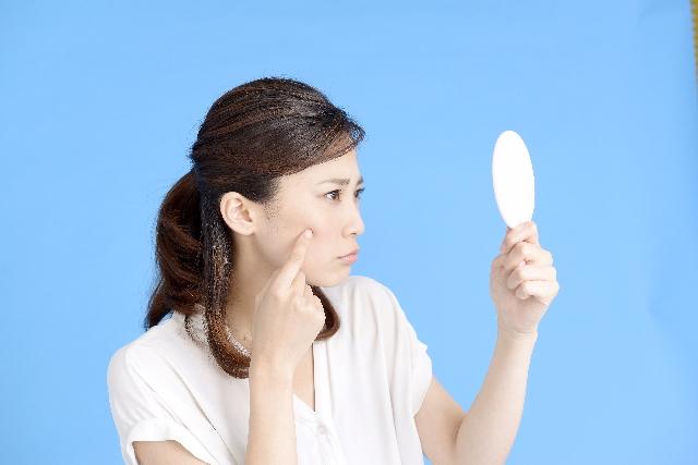 鏡を見ながら肌をチェックする女性