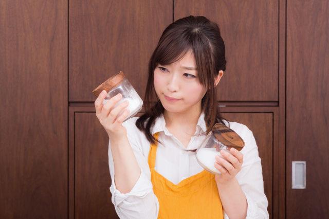 塩と砂糖を見比べる主婦