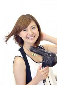 ドライヤーで髪の毛を乾かしている女性