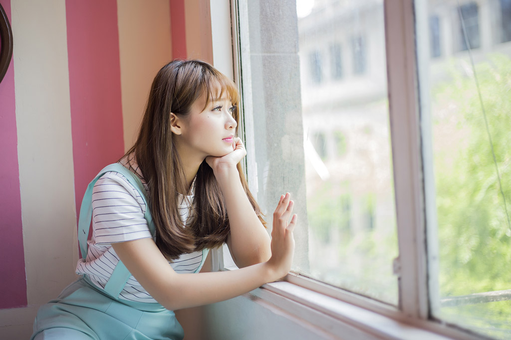 窓辺に肘をつき外を眺める半袖の女の子