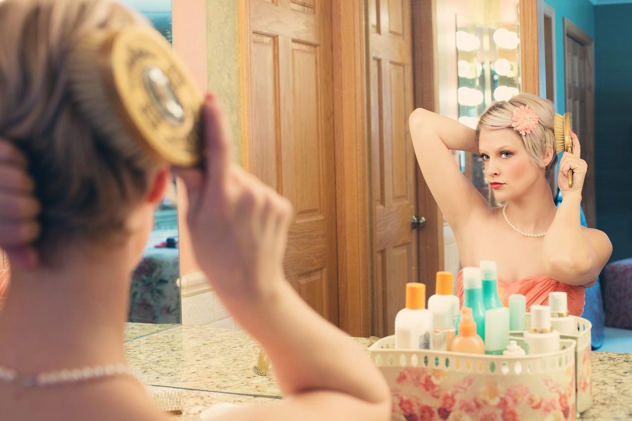 鏡の前でヘアブラッシングをしながら肘の黒ずみをチェックする女性