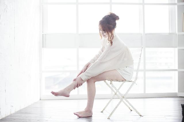 椅子に座りながら足をセルフマッサージする女性