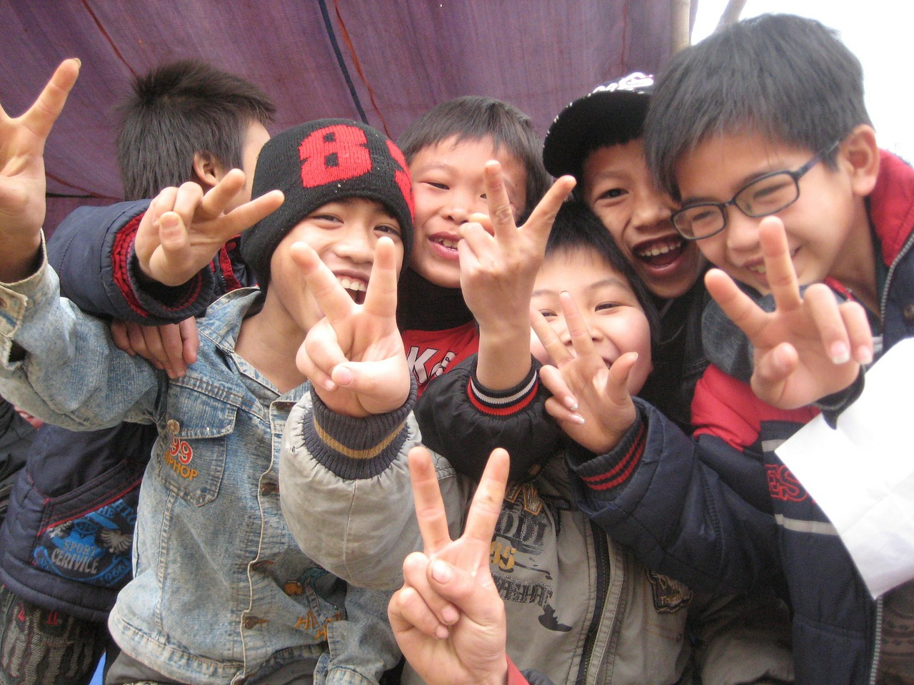 ピースサインをする笑顔の子供たち