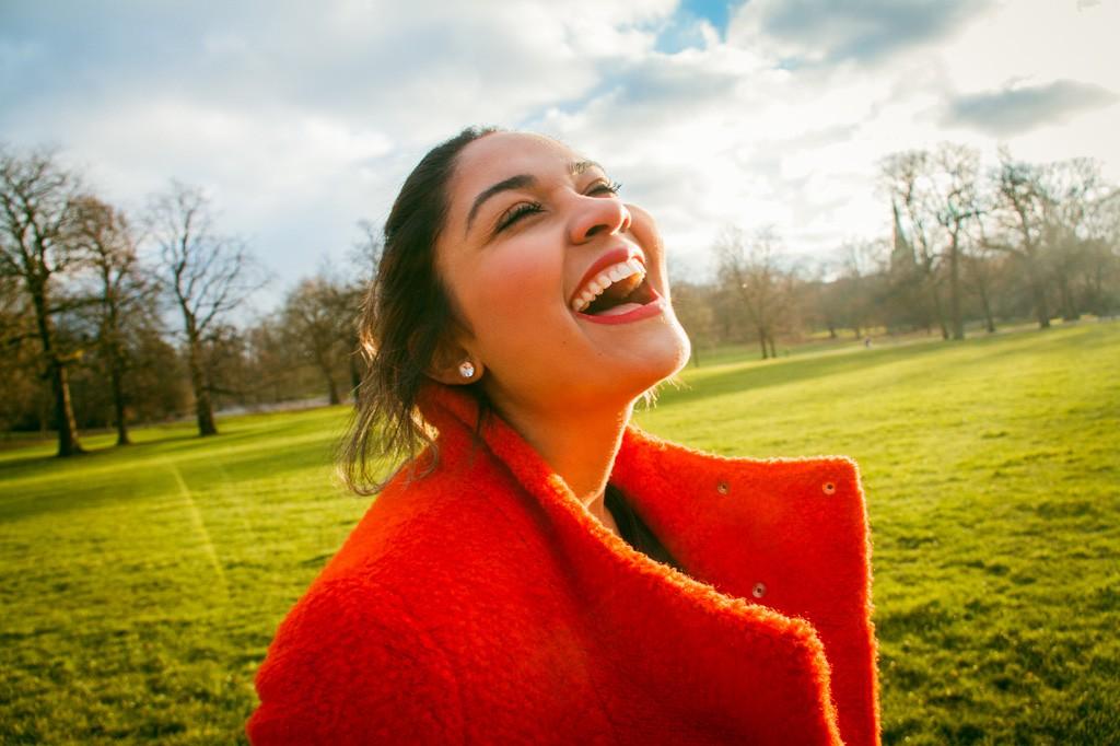 満面の笑みで喜んでいる赤いコートを着た女性