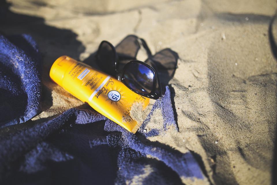 砂の上に置かれたUVケアアイテム