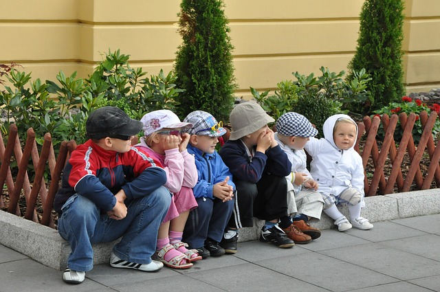 花壇に腰掛ける幼い子供たち
