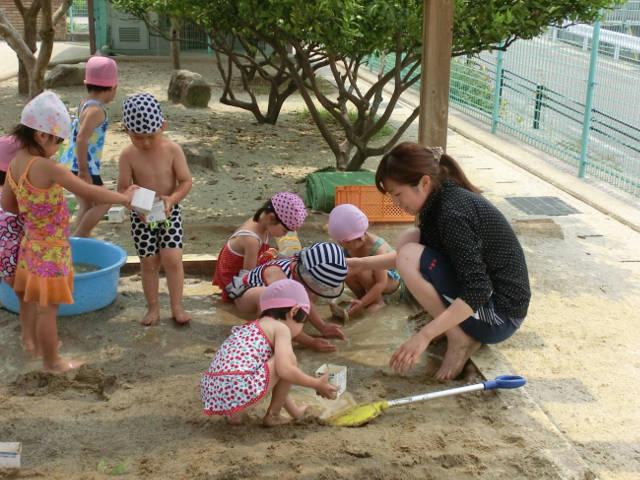 砂場で水遊びをする園児と先生