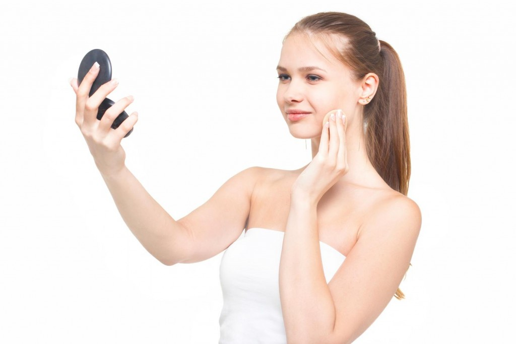 手鏡を見ながらファンデーションを塗る女性