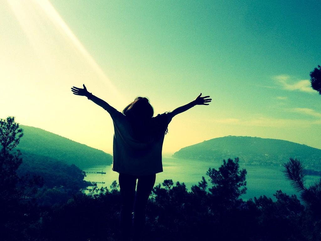 大自然の景色を見ながら、両手を大きく広げている女性