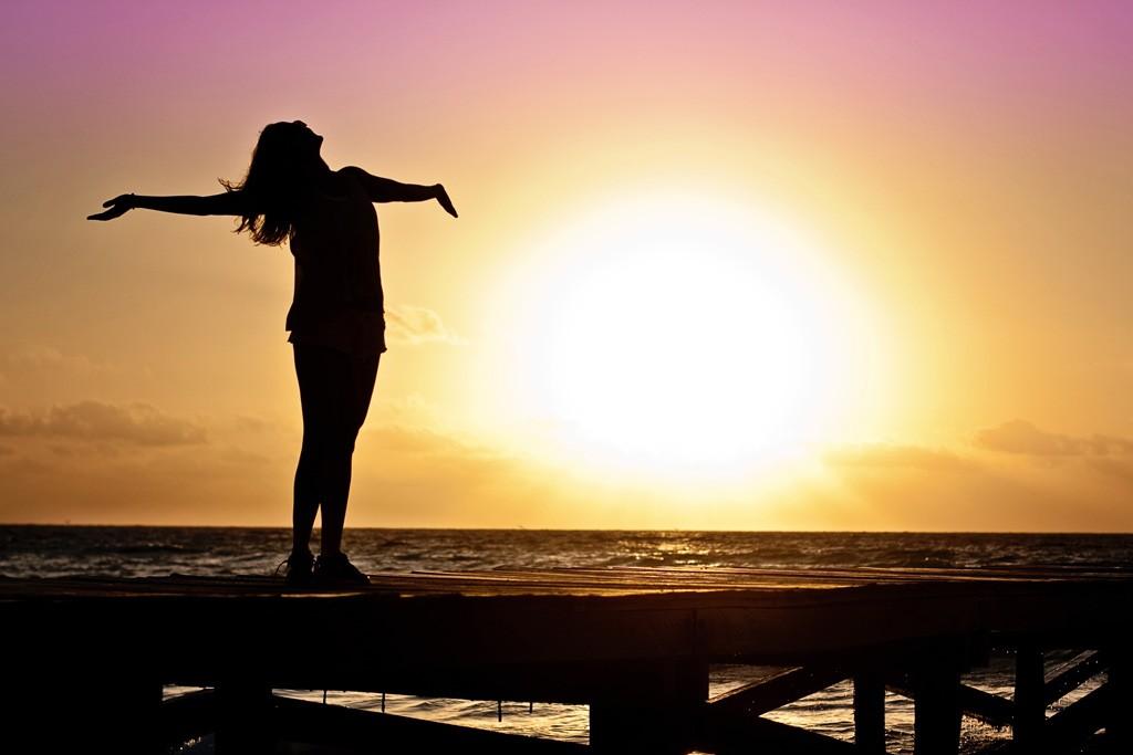 身体全体で夕陽を感じながら、海辺で深呼吸をしている女性