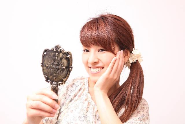 手鏡を見て笑顔の女性