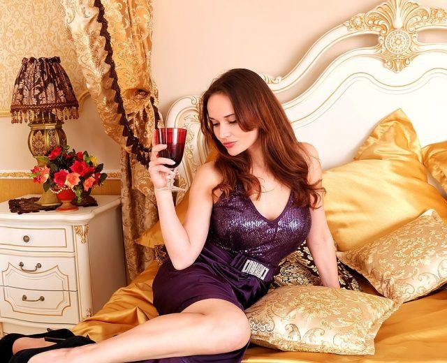 ベッドでお酒を飲む女性