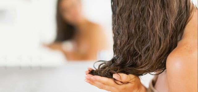 髪にトリートメントを塗る女性