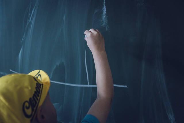 黒板にチョークで書く男の子