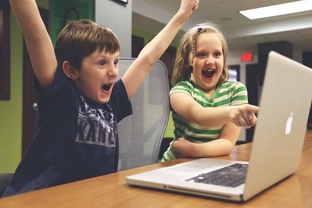 パソコンを前で喜ぶ男の子と女の子