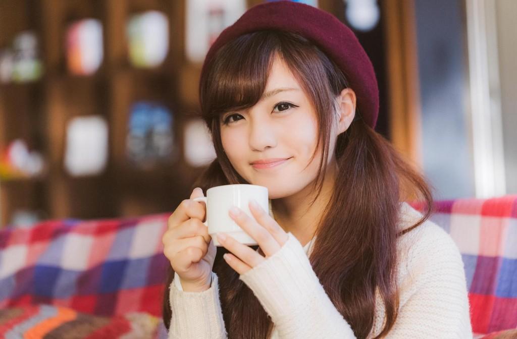 両手でマグカップを持っている笑顔の若い女性