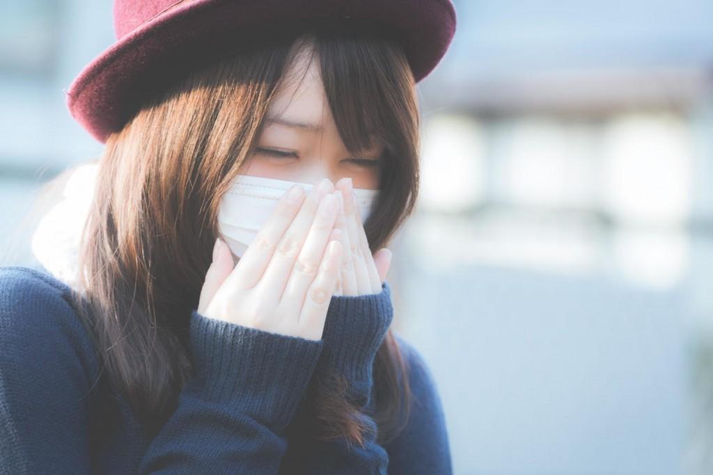 マスクの上から手で口を押えてくしゃみをしている女性