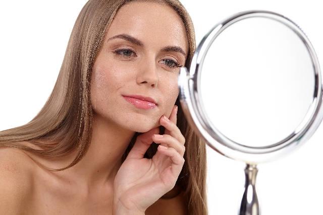 鏡で化粧をチェックする女性