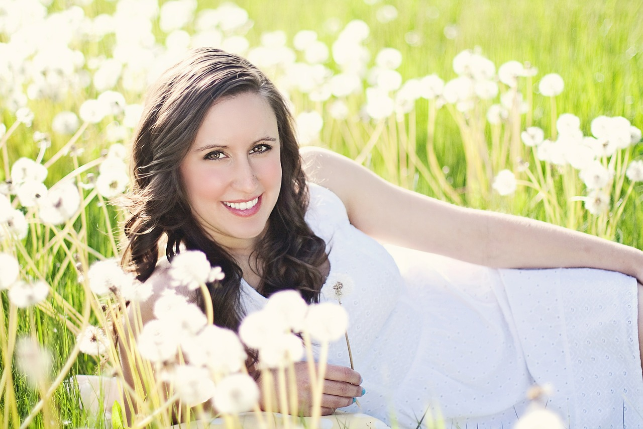 牧草地の花に囲まれているドレス姿の女性