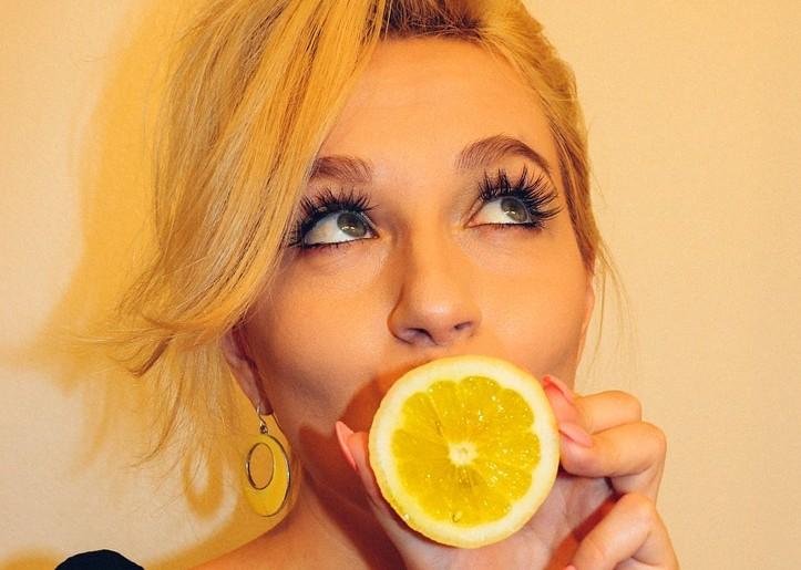レモンで口を隠している30代~40代くらいの金髪の女性